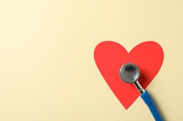 Стетоскоп и сердце на бежевом фоне, крупным планом. здравоохранение