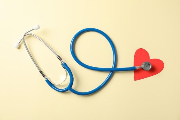 Стетоскоп и сердце на бежевом фоне, пространство для текста. здравоохранение