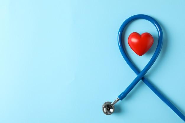 Стетоскоп и сердце на синем фоне, вид сверху