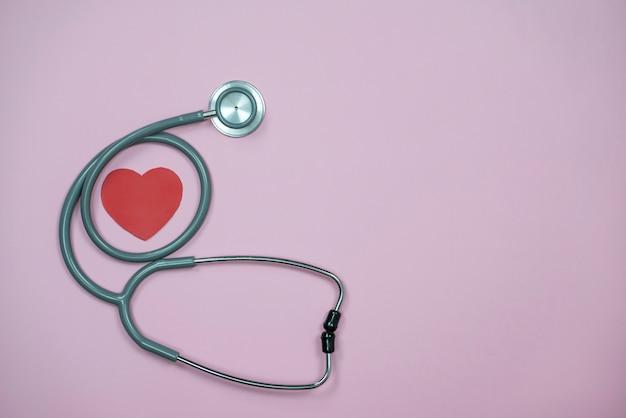 Стетоскоп и сердце на пастельно-розовом фоне с копией пространства