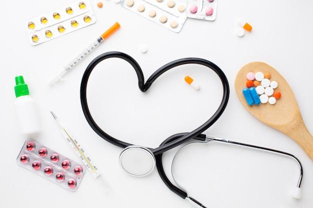 Стетоскоп и медицинские таблетки со шприцем
