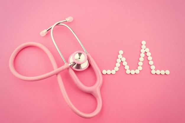 Стетоскоп и таблетки в форме пульса на розовом столе