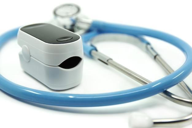 白い背景で隔離聴診器とパルスオキシメータcovid19ヘルスケアの概念