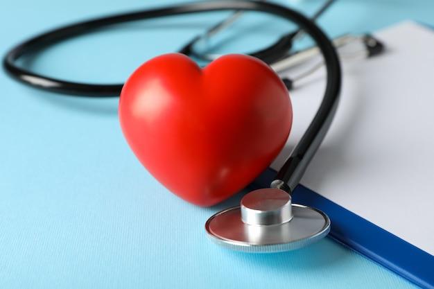 聴診器と青い表面に赤いハートをクローズアップ。健康管理