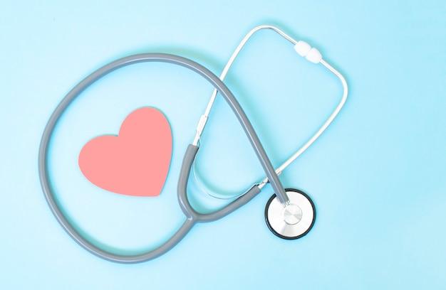 Стетоскоп и форма красного сердца на синем фоне, концепция сердца и здравоохранения