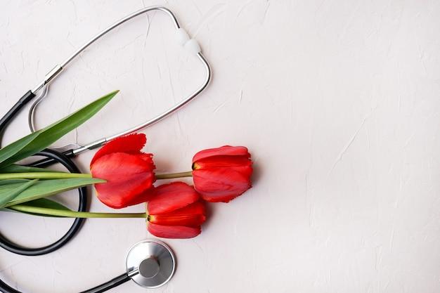 Стетоскоп и красные тюльпаны на белом фоне. копировать пространство