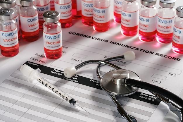 聴診器とワクチン接種のための背景にワクチンバイアルガラス瓶