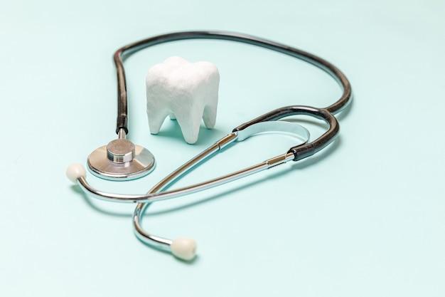 청진 기 및 파스텔 파란색 배경에 고립 된 흰색 건강한 치아