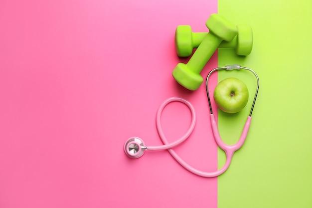 Стетоскоп, яблоко и гантели на цветном фоне