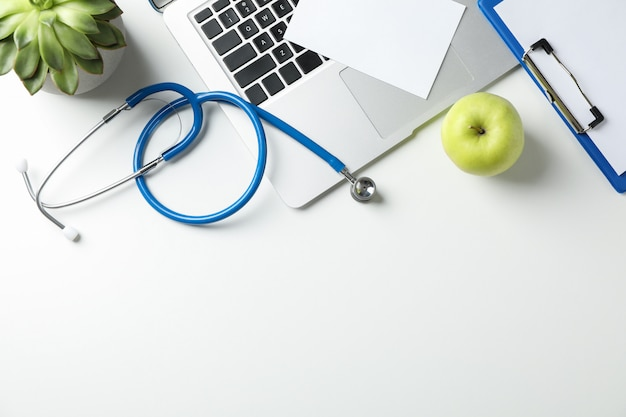 Stethoscope, apple, laptop and plant on white background, top view. doctor workplace