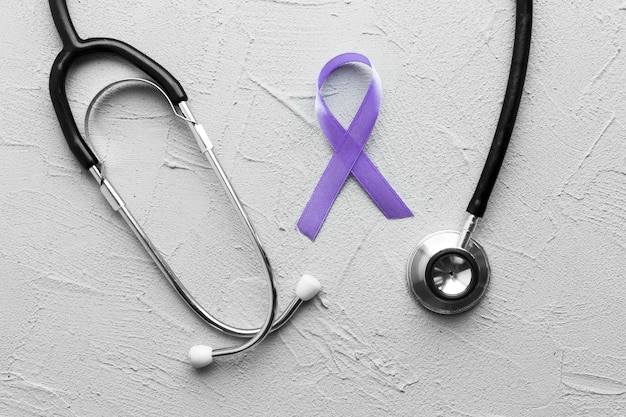 Стетоскоп вокруг фиолетовой ленты на гипсе