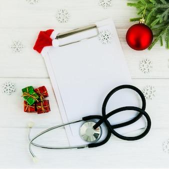 청진 기, 빈 클립 보드 및 나무 흰색 테이블에 크리스마스 장식. 의료 개념. 인사말 카드. 새해와 크리스마스.