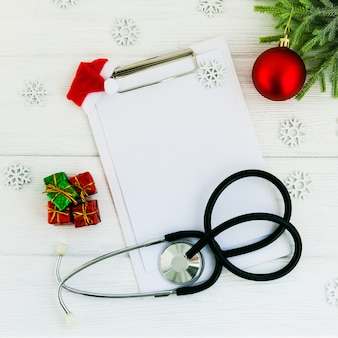 Stethoscope, blank clipboard and christmas decorations on wooden white table. medical concept. greeting card. new year and christmas.