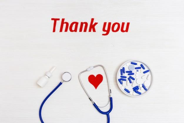 聴診器ブルー色、錠剤、赤いハート、コピースペースを持つ白い木製の背景に「ありがとう」のテキスト。医療スタッフへの感謝の言葉。