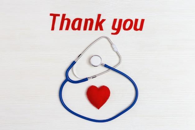 Стетоскоп синего цвета, красное сердце и надпись «спасибо» на белом дереве