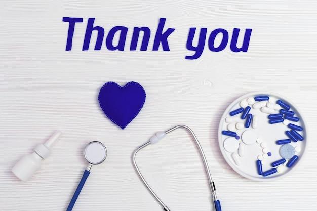 聴診器、青いハート、点鼻薬、錠剤、白い木製の表面に「ありがとう」のテキスト