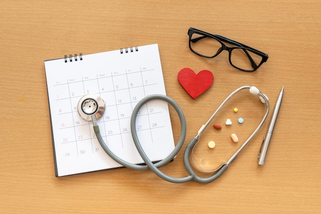 Stethoscope and calendar on wooden table, schedule to check up healthy concept