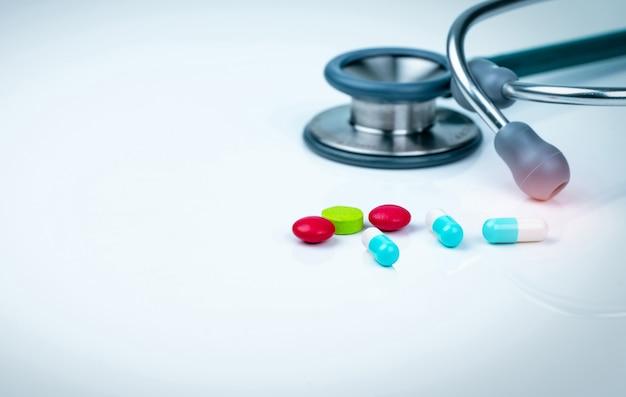 ドクターテーブルまたは看護師の机の上の聴診器、カプセル、錠剤の錠剤。健康診断。医療ヘルスケアおよび医学。患者診断のための医師ツール。心臓病の医者の機器。