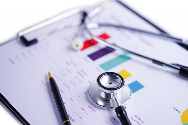 Stethoscope on charts and graphs spreadsheet paper.