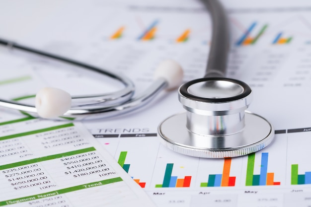 Stethoscope on charts and graphs spreadsheet paper