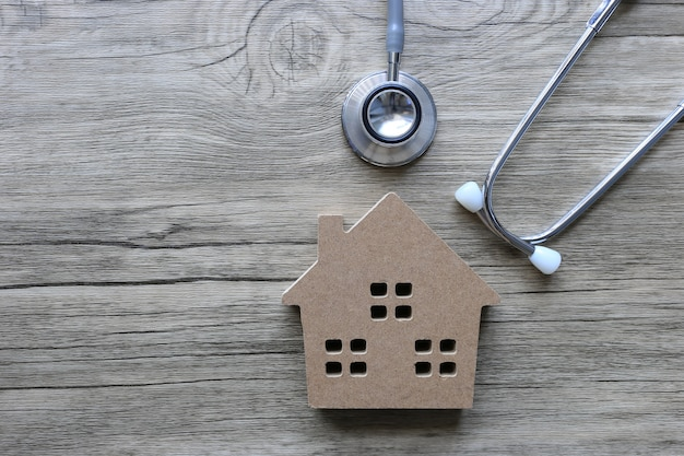 Stethoscope to check model house on wooden table