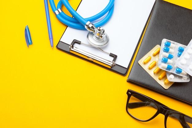 Stethoscope, clipboard and pills, closeup, medical equipment