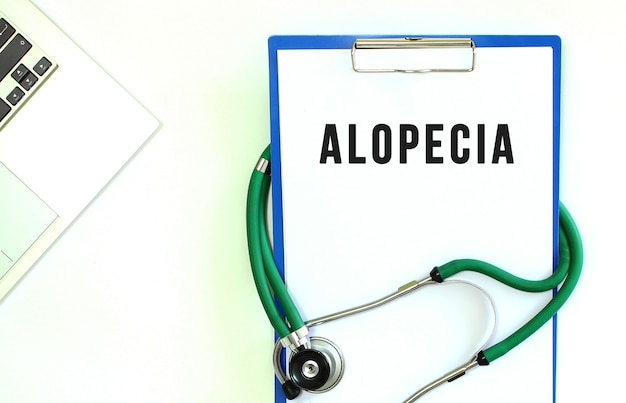 Stethoscope and clipboard with alopecia text on white sheet of paper and copy space.