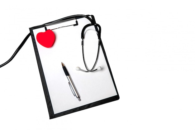 Stethoscope, clipboard with medical form lying on hospital reception desk