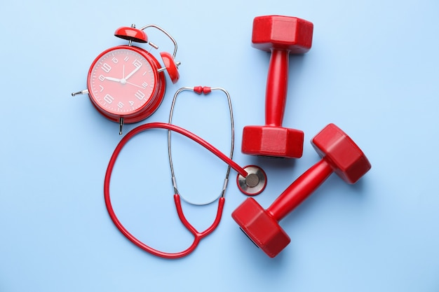 Stethoscope, clock and dumbbells on color background