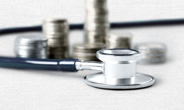 Stethoscope on currency coins on light background