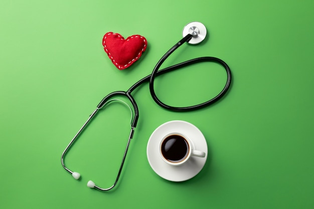 Stethoscope in doctors desk with cup coffee and heart. top view.