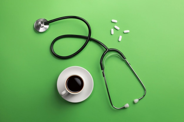 Stethoscope in doctors desk with cup coffee and pills. top view.