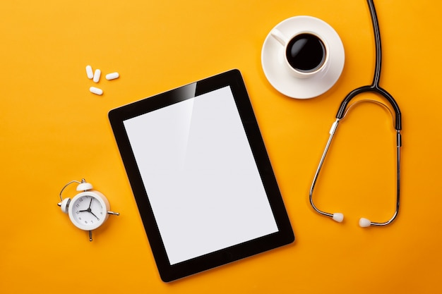 Stethoscope in doctors desk with digital tablet, coffee cup, alarm clock and pills