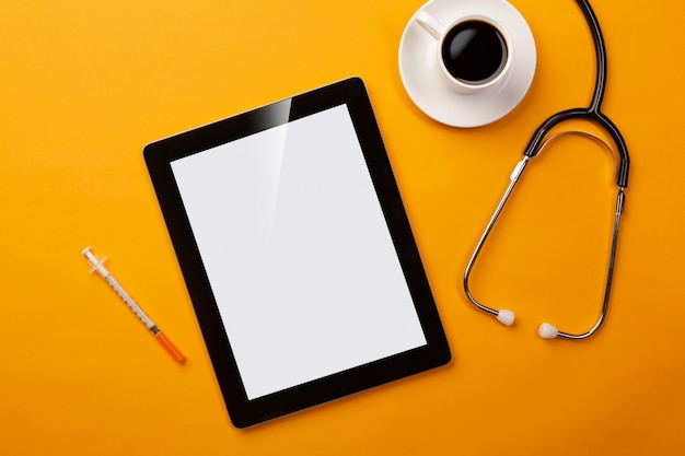 Stethoscope in doctors desk with digital tablet, coffee cup, syringe and pills