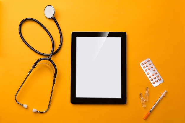 Stethoscope in doctors desk with digital tablet, syringe and pills