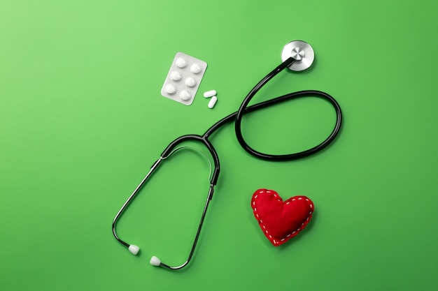Stethoscope in doctors desk with heart and pills. top view.