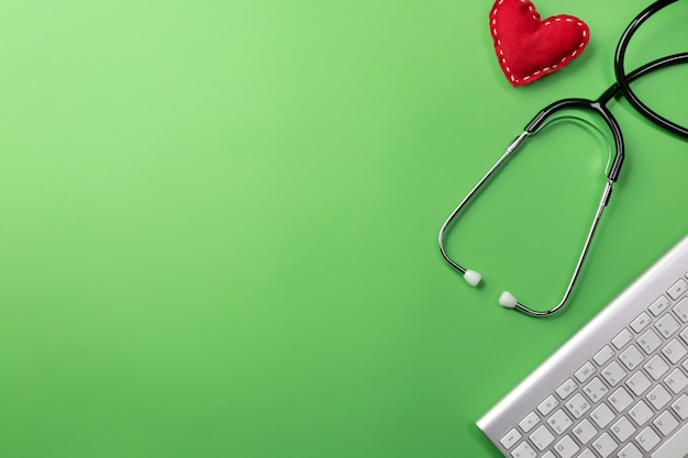 Stethoscope in doctors desk with keyboard and heart background