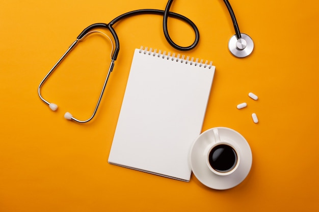Stethoscope in doctors desk with notebook, coffee cup and pills. top view with place for your text.