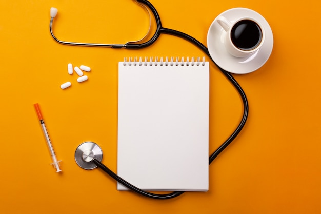 Stethoscope in doctors desk with notebook, coffee cup and pills, top view