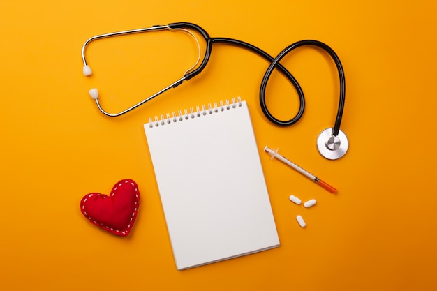 Stethoscope in doctors desk with notebook and heart