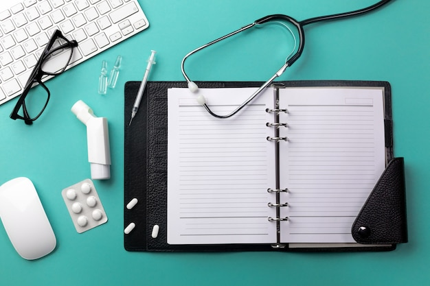 Stethoscope in doctors desk with notebook, keyboard, mouse, glasses, syringe, ampoules, inhaler and pills. top view with place for your text.
