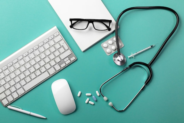 Stethoscope in doctors desk with notebook, pen, keyboard, mouse and pills. top view with place for your text.