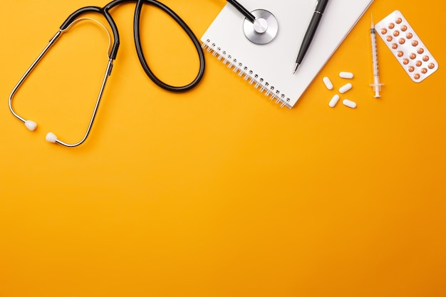 Stethoscope in doctors desk with notebook and pills. top view with place for your text.