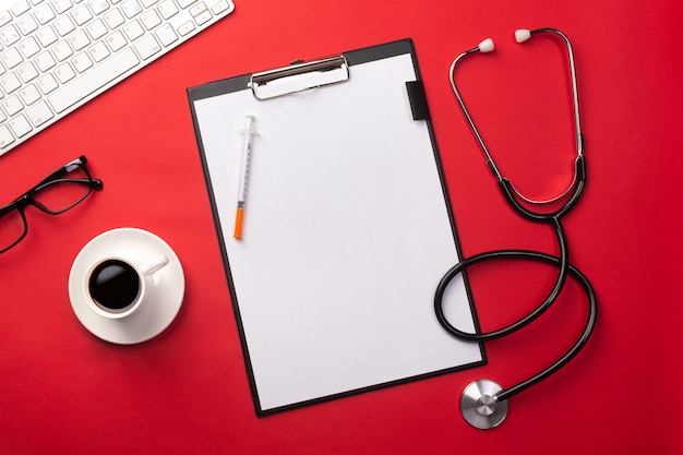 Stethoscope in doctors desk with tablet and coffee cup, top view