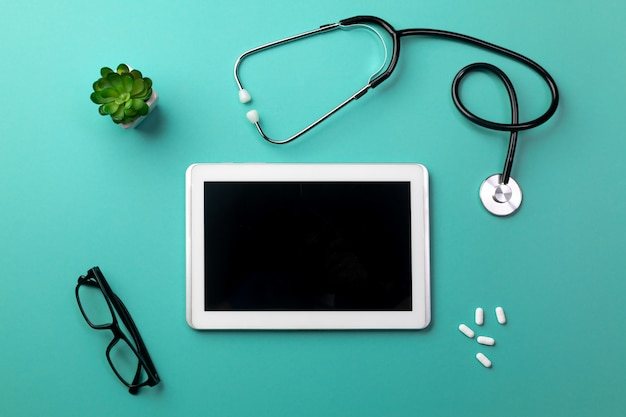 Stethoscope in doctors desk with tablet, glasses and pills