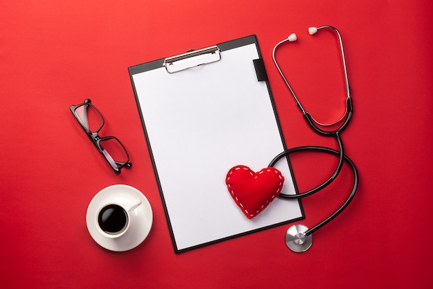 Stethoscope in doctors desk with tablet, heart and coffee cup, top view