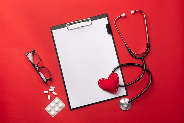 Stethoscope in doctors desk with tablet, heart and pills