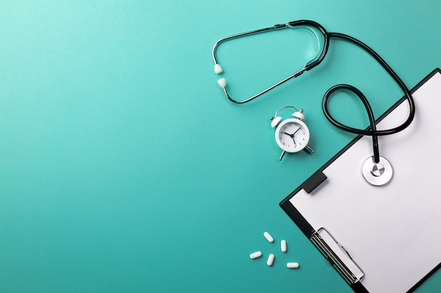 Stethoscope in doctors desk with tablet, pen and pills. top view with place for your text.