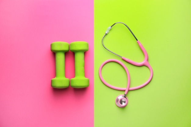 Stethoscope and dumbbells on color background