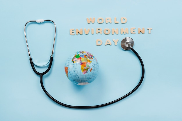 Stethoscope and earth planet on blue background